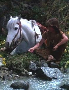 Gourgous up-close shot of Atreyu sitting by the stream giving Artax his breakfast while enjoying a strip of dried buffalo meat. Old Movies, Great Movies, 1980s Films, The Neverending Story, Beautiful Places To Live, Fiction Movies, Drawing Projects, Story Characters, Daily Drawing