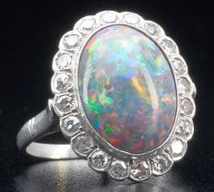 Art Deco multi-color black opal and diamond ring in pt., with a bright oval stone surrounded by twenty single-cut diamonds. Opal: approx. 4.2 cts, 15.25 mm x 11 mm x 5 mm.