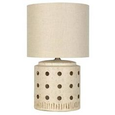 The neutral tones and barrel shapes get a punch of style in the Ceramic Cut Out Table Lamp from Nate Berkus. This beige table lamp has a perforated base with etched markings below.
