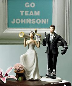 "Cheering Bride & Hockey Player Groom Wedding Cake Topper made of hand painted porcelain. The bride is wearing a white dress holding a mega phone and a ""#1 Fan"" hand. The groom is wearing a black tux with ice skates and gloves while holding a hockey helmet and a hockey stick."
