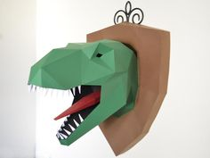 Big game hunter? Go prehistoric with this wall trophy of a tyrannosaurus! All you need is paper, glue, and our PDF pattern! This dinosaur trophy is sure to start conversations and makes a fun DIY project.  Approximate Dimensions: 22 in. tall, 17 in. wide, and 18.5 in. front to back (with shield)  Difficulty Level: Medium-Hard Pages: 22   This purchase is for the pattern and instructions only. You will need card stock or other material, access to a printer, scissors or a craft knife, and glue…