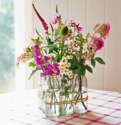 Simple flower arranging bottles tied with twine.
