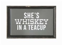 "Add a little Southern Sass to your walls with our ""She's Whiskey In A Teacup"" sign! Perfect in any farmhouse kitchen! Measures: 12""L x 8""H Materials: Wood frame, glass"