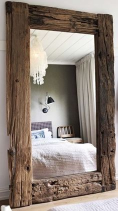 A full length mirror framed in old wood.