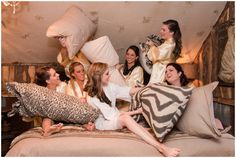 Bridesmaids have pillow fight in honeymoon suite of barn at Twisted Ranch near Georgetown, Texas