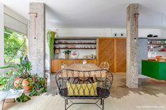 Sala de jantar com portas de correr de madeira e lousa, bancos de ferro e mesa de madeira rústica.