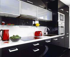 En negro con armarios hasta el techo. Bonitos toques de color en los pequeños electrodomésticos. Encimera blanca. A tener en cuenta!
