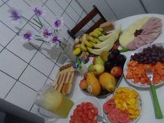 Hummm...café da manhã de uma Rainha <3 . Lave as frutas e corte-as em cubinhos ajeitando-as em pratos...acomode tbém os pães e biscoitos numa travessa ...fica mais bonito... ;) sua mãe vai perceber todo esse carinho.