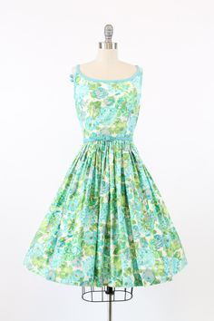 Summer perfect 1950s dress! Done in a quality cotton sateen printed with blue zinnias, roses and other flowers. Turquoise cotton trim along the neckline, thin straps, and around to the low back that has two sweet bows. Fitted waist and gathered full skirt. Back zipper. Comes with matching thin belt. Bodice is lined in cotton, skirt is unlined.  ♥♥♥ Brand: the look new york Size on tag: None Fits like: XS Color: white/blue/green Material: cotton Condition: Excellent Vintage: zipper ...