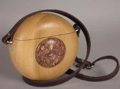 """Betel Bag - Whimsical canteen  style shoulder bag of poplar with  curious inset of sliced betel nut  and epoxy.  No one has one like  this.   Unlined, brown leather  strap. 8.5"""" diameter, 4"""" thick."""