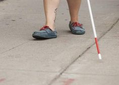 A pair of feet walk down a sidewalk, with a white cane tapping ahead.
