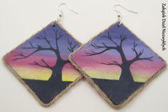 """Kolczyki z kolekcji """"Gdy słońce zachodzi"""" - romby o przekątnej/średnicy 7 cm, z drewnianej sklejki, ręcznie malowane farbą akrylową z obu stron, w odcieniach fioletu, z motywem drzewa, zabezpieczone lakierem, zdobione sznurkiem jutowym, na otwartych biglach. Dzieło Wielkiego Słonia w Czerwone Paski."""