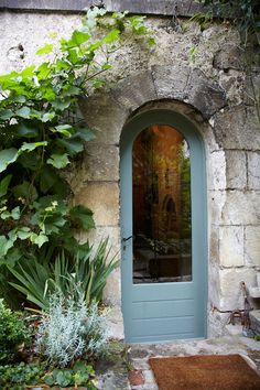Home Tour: Celine Chollet's Rustic French Home—A curved blue door punctuates the rustic, stone entrance.