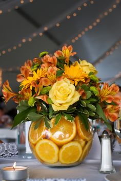 With yellow roses and marigold gerbera daisies topping a vase filled with orange slices, this bright centerpieces brings energy to the table.