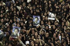 In Monday, Sept. 30, 2002 file photo, #Iranian #women hold pictures of President Mohammad #Khatami during a public welcoming ceremony at the Azadi stadium in the city of #Rasht