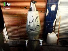 """Repurposing tools of destruction.   A water tank in the Damascus suburb of Douma is fashioned from a bomb. The slogan reads, """"I am the drink of freedom."""""""