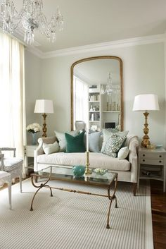 Light green walls paint color, floor length gold mirror, Sarah Richardson Nicole Sofa with green pillows, antique brass glass-top cocktail table, antique gold lamps and white end tables.