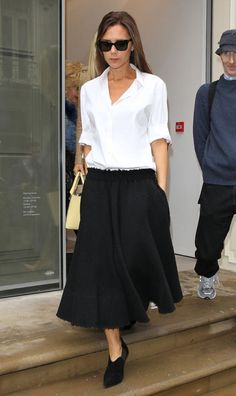Victoria Beckham in a white shirt and black skirt