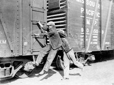 Teenagers hopping on a freight train during the Great Depression ca. 1930s