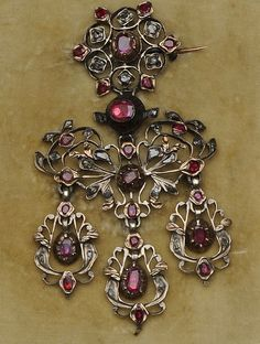 A late 18th century ruby and diamond girandole brooch/pendant  The openwork pendant of foliate chandelier design, set throughout with oval and circular-cut rubies and rose-cut diamonds in foiled closed back settings, with three pendant drops below, length 8.3cm [I really wish they wouldn't photograph these in their box. Makes them look dirty.]