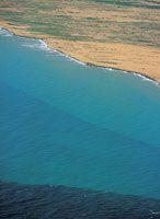 Aporte de sedimentos de suelo arcilloso que se depositan en el mar y contribuyen a aumentar la turbidez de las aguas.