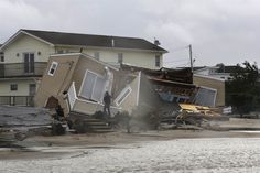 A man photographs a home damaged during a storm at Breezy Point in the New York City borough of Queens on Tuesday. The fire destroyed between 80 and 100 houses Monday night in an area flooded by Hurricane Sandy. Breezy Point, Flooded House, Todays Weather, Hurricane Sandy, Natural Disasters, East Coast, Climate Change, New York City, Fire
