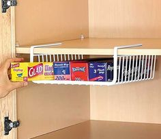 An easy kitchen space saving trick is to hang baskets in your cupboards to store your foil and saran wrap there.