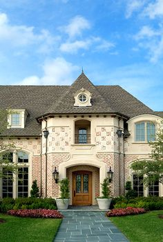 French Normandy style home with checkerboard detail in brick & cast stone...