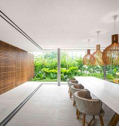 salle à manger contemporaine avec des panneaux treillis bois d'occultation, chaises en bois tapissées et des suspensions en bois