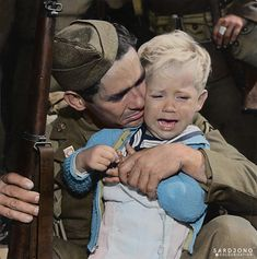 U.S. Private John G. Winbury gives a hug to his son Robert Austin Winbury, as he prepares to sail to Hawaii with the California 251st Coast Artillery, National Guard, 31 October 1940. He survived the war. : Colorization