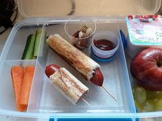 Frankfurters wrapped in bread and toasted, carrot and cucumber sticks, dipping sauce, nuts, yogurt and fruit.