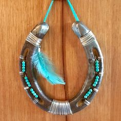 My latest make. What do y'all think? #horseshoe #artsandcrafts #tourquoise #beads #feathers #silver #shoe #equine #horselovers