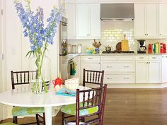 This North Carolina home's kitchen cabinets and backsplash allow the bold fabric choices in the breakfast area to shine. Colorful accessories, cookbooks, and dish towels, keep an all-white kitchen from feeling stale or industrial. (Photo: Laurey W. Glenn)