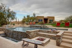 Contemporary Swimming Pool with Outdoor kitchen, Pool with hot tub, exterior stone floors, Fire pit, Fence, Raised beds
