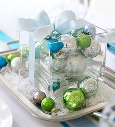 Christmas centerpiece: silver tray, white paper shred or fake snow, square glass vase, ribbon, various size Christmas balls in lime green, silver, and turquoise.