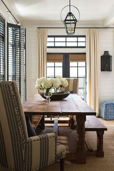 The dining table and benches were custom built from reclaimed barn wood. Interior designer Betsy Berner selected upholsted captain's…