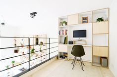 Home office with organized shelving and Eames chair that overlooks kitchen