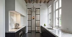 Designed by the Belgian company Obumex- Isn't it gorgeous? I love the contrast of black and white and the earthy tone of the beamed ceiling, the steel pocket door and not to forget the beautiful chandelier.
