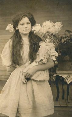 PHOTOGRAPHY: Long haired Girl and her doll with a large flower hat. The girl's age is not given, but given her size posing for a formal portrait picture with a doll is unusual. The doll, however appears to be an expensive one. More likely it is a trophy rather than plaything.