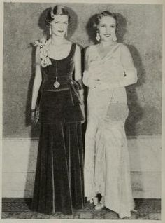 Photoplay - December 1930: Joan Bennett and Bessie Love at the first Mayfair Party. Two little girls out of school and all dressed up for the first Mayfair party at the Los Angeles Baltimore Hotel, where 500 made merry.  Joan Bennett left, wears a tiered gown of purple velvet, with a spray of orchids.  Bessie Love's new and charming party frock is of white ruffled satin.