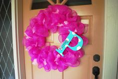 Wooden letter painted with polka dots decorates a bright pink deco mesh wreath