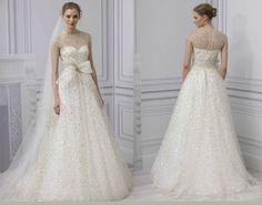 Creme de la Creme of the selection from Monique Lhuillier Spring 2013 Bridal Collection is Champagne. This gown will transform any bride to a glorious glitter goddess! Silk A-line gown with gold embroidered tulle and illusion cap sleeve gown with a bow belt to cinch in the waist. Bling!