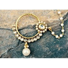 This nose ring is made of an alloy and embellished with diamonds. It's plated with antique gold polish and accented with a pretty kundan ruby flower that is bordered by pearls. The nose ring requires a pierced ear. Also has a lovely pearl string that is hooked up to the hair. Pair with ethnic Indian clothing and wear to ceremonies or weddings. -https://www.cooliyo.com/product/73416/round-nose-ring-with-flower-accent-and-pearl-drop/