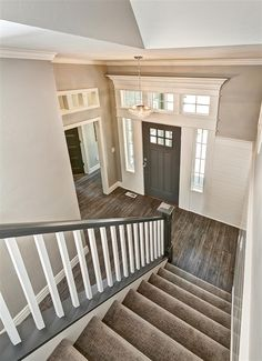 Entryway with gray stair rail and white ballusters. Crystal entry chandelier. Tuftex carpet with Manningtons Restoration Collection laminate flooring in Black Forest Oak fumed. Benjamin Moore Kendal Charcoal front door with White Dove trim. Transom windows above door frames.