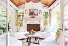 Neutral indoor-outdoor living space with white furniture, fireplace, and Wizard of Oz on the TV