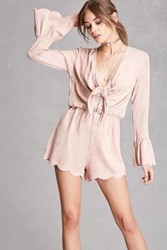 A knit faux suede romper by Selfie Leslie™ featuring long sleeves with scalloped trumpet cuffs, a V-neckline with a tie front and a button-down placket, an elasticized waist, and a scalloped hem.
