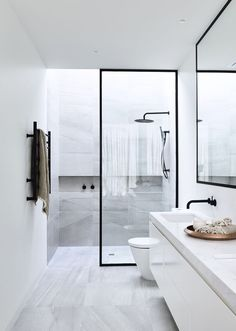 a modern space with grey marble tiles, white cabinets, black frame glass door and faucets
