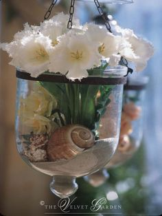 Beach theme wedding: hanging vases with flowers, shells, and sand. This would work in hurricane vases too.