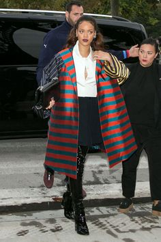 In an oversized striped coat, Chanel bag, white blouse, black pants and black Dior over-the-knee boots in Paris