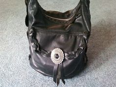 Hand made black leather purse with silver hardware and braided handle.
